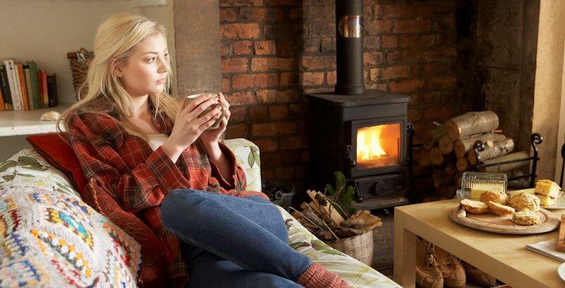 暖炉であたたまる女性